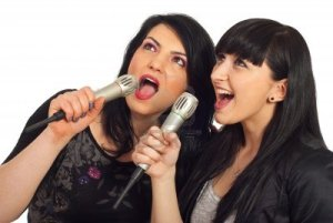 9233768-happy-beauty-two-women-singing-in-microphones-at-karaoke-party-and-looking-up-to-screen-isolated-on-